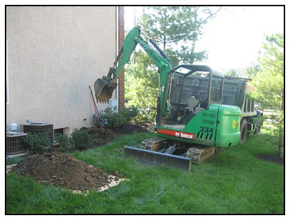 Excavators removing dirt for installation of the egress window