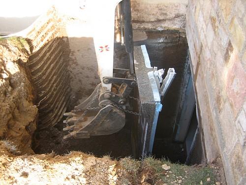 Crane making opening for basement egress installation