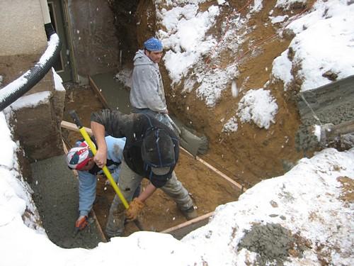 Men digging up ground for egress system installation