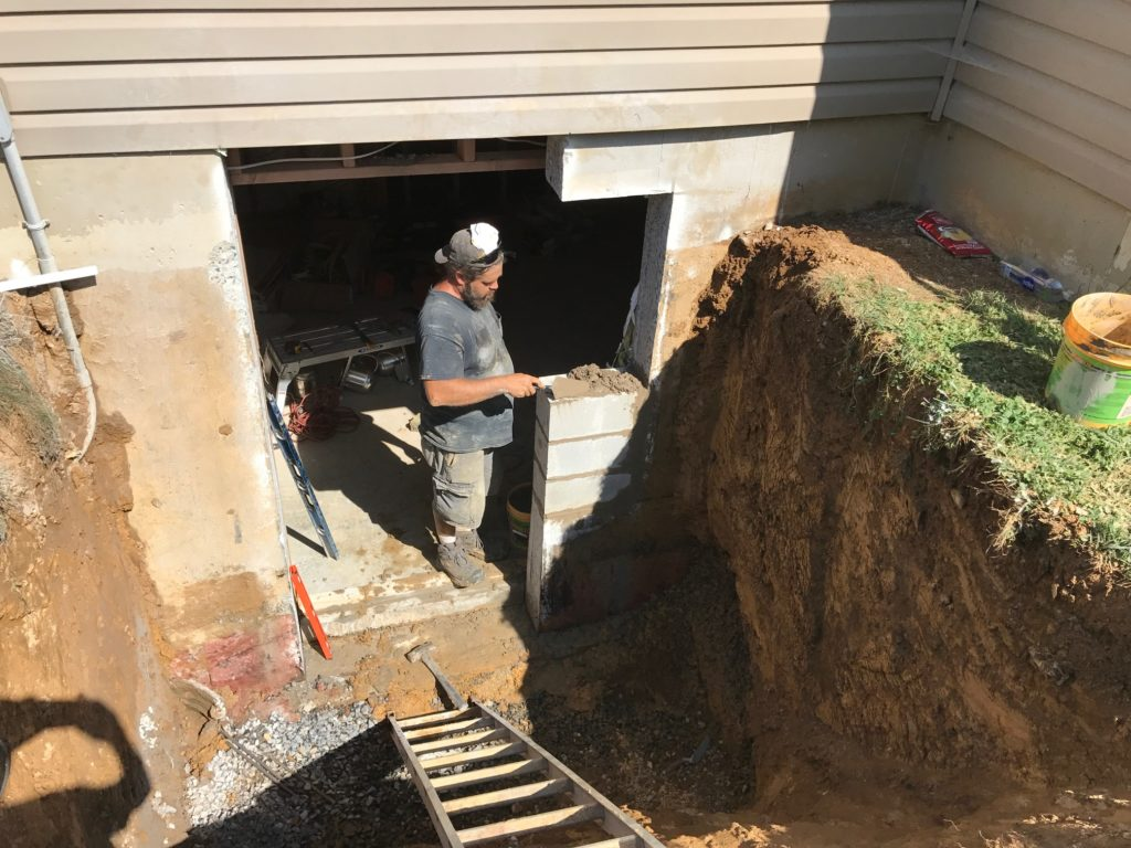 A worker is working on the basement entrance construction