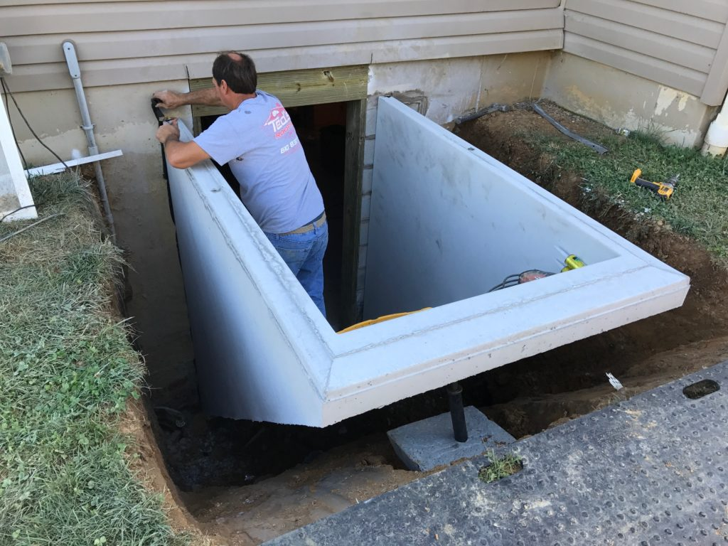 A worker is working on installing the basement entrance
