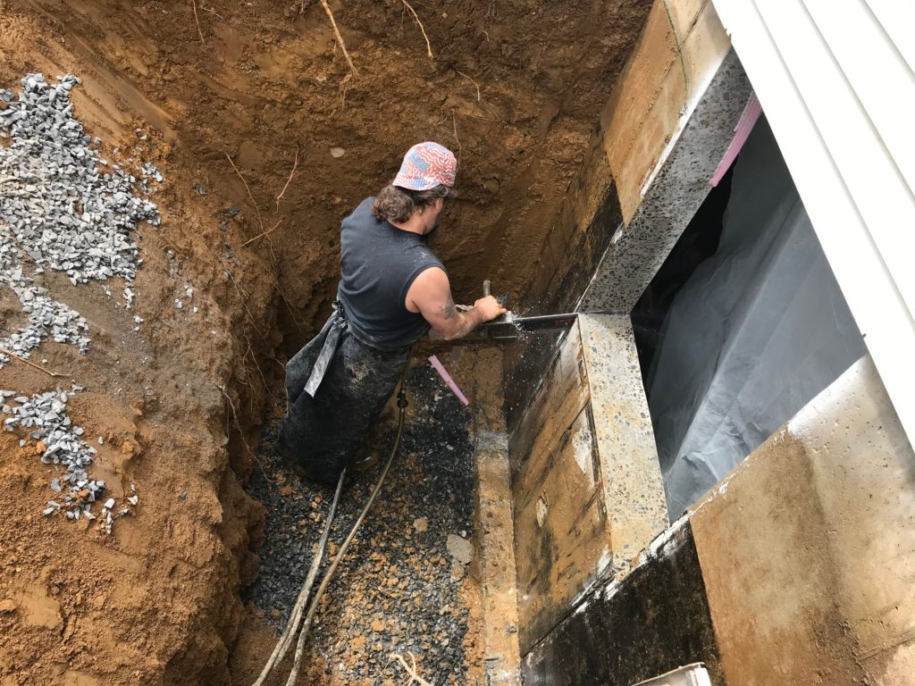 A worker is working on creating the basement emergence entrance