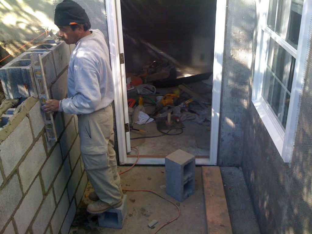 The worker is installing the wall tile for the customer's basement permentry egress project