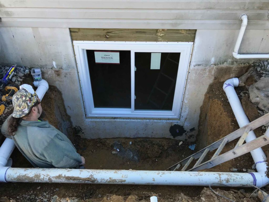 Excavated hole and installed egress door