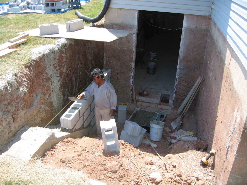 The worker is laying the foundations for basement escape staircase