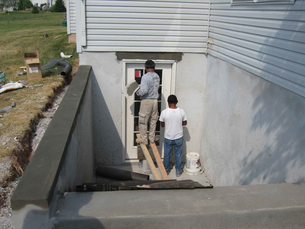 Two workers are working on installing lightweight door